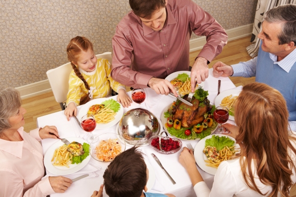 Image of big family sitting at festive table and eating salad and roasted turkey